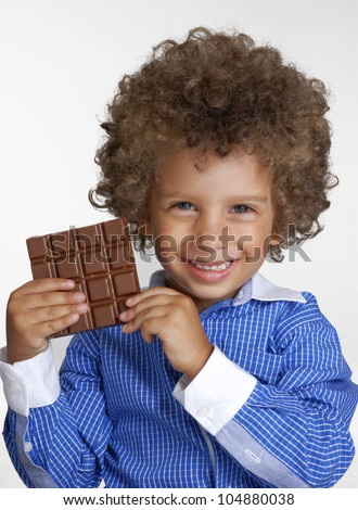 Little kid eating chocolate,holding chocolate bar.