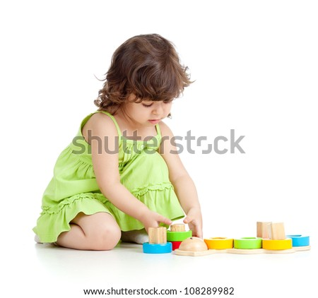 little kid girl playing with colorful toys, isolated over white