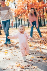 little kid girl runs in autumnal couple and plays with parents. toddler runs away on autumn yellow leaves from mother with father