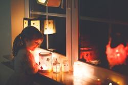 Little kid girl sitting by window with selfmade hand crafted lanterns with candles for St. Martin procession. Toddler child looking at glowing lantern. German tradition Martinsumzug. Home decoration