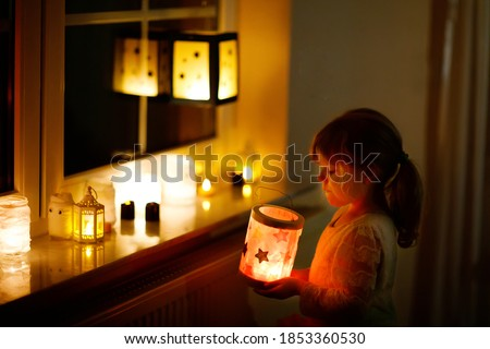 Little kid girl sitting by window with selfmade hand crafted lanterns with candles for St. Martin procession. Toddler child looking at glowing lantern. German tradition Martinsumzug. Home decoration ストックフォト ©