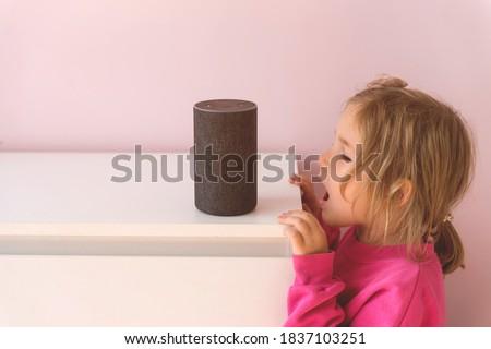 Little kid girl talking to talking to Amazon Alexa Echo Dot. Education programme for child. kid girl talking to Alexa and give it orders and commands what to switch on.