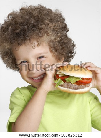Little kid holding a big hamburger,eating hamburger.