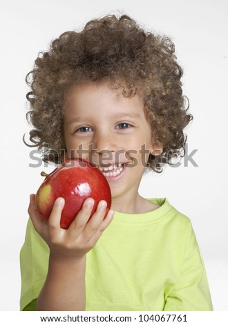 Little kid holding a red apple,eating apple.