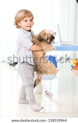 little kid holding his pet at home, two years old child playing with his dog in the living room #138539864