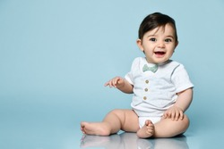 Little kid in white bodysuit as vest with bow-tie, barefoot. He is smiling, sitting on floor against blue studio background. Concept for articles about childhood or advertising for babies. Close up