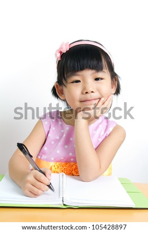 Little kid is doing her home work with smiling face