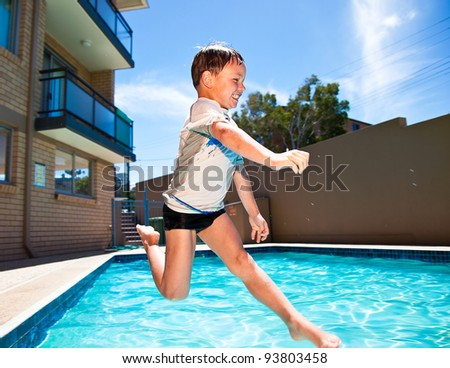 Little kid jumping into a swimming pool