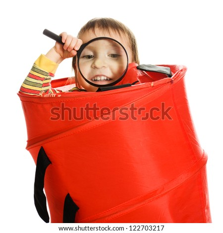 Little kid looking out of basket with a magnifying glass on a white background.