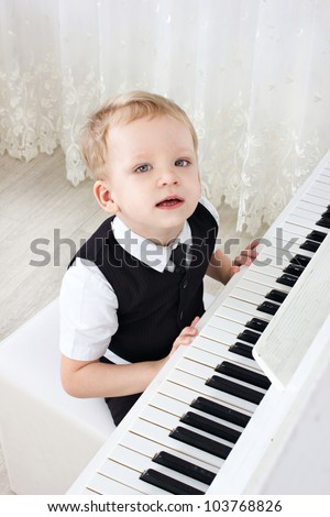 little kid near the piano in the room looking at camera