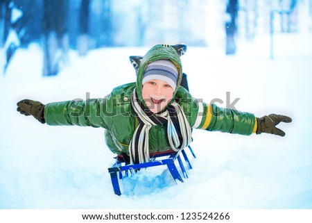 Little kid on sleigh. winter