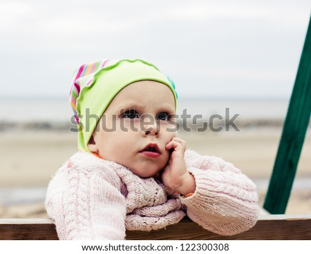 Little kid on the beach dreaming of summer.