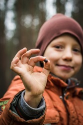 little kid playing in green forest looking to camera showing ok sign close up. small confident boy in nature surroundings wild free lifestyle copy space.