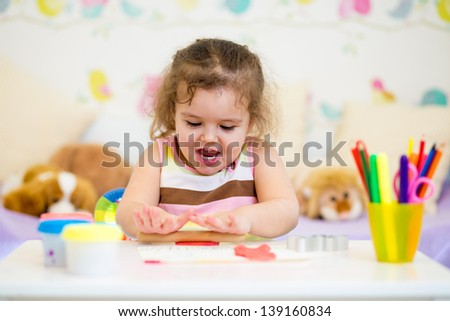 Little kid playing with colorful clay