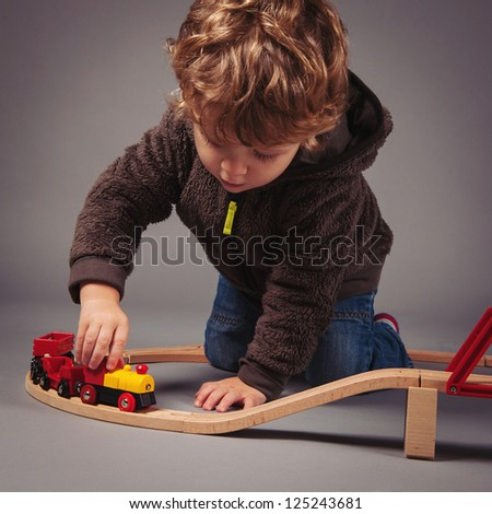 Little kid playing with train construction. Studio shot.