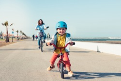Little kid riding a balance bike with his mother on a bicycle in a city park