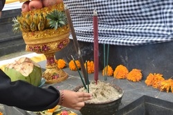 Little kid's hand giving incense Hinduism offering in ceremony.  Selective focus.