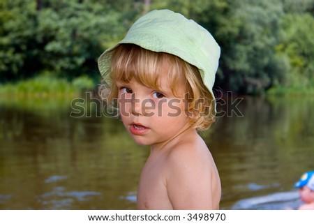 Little kid stands near river