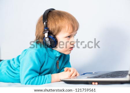 Little kid watching a movie on laptop computer with headphones on his head