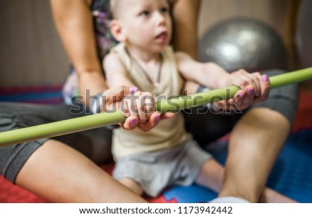 little kid with cerebral palsy has musculoskeletal therapy by doing exercises in body fixing. Load on hands