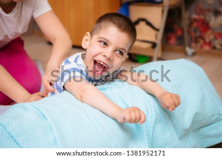 little kid with cerebral palsy has musculoskeletal therapy by doing exercises in body fixing. Load on hands,cheerful boy with disability at rehabilitation center for kids with special needs Stock photo ©
