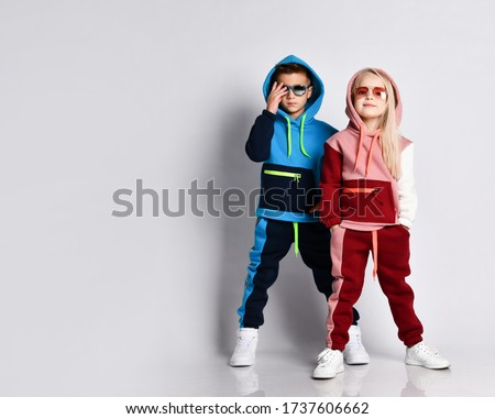 Little kids, boy and girl, in sunglasses and hoods, colorful tracksuits, sneakers. They posing isolated on white studio background. Childhood, fashion, advertising and sport. Full length, copy space
