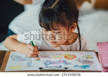 Little kids drawing cartoon with her color pencil that is good activity for improve creative art and hand writing skills in children. Foto stock ©