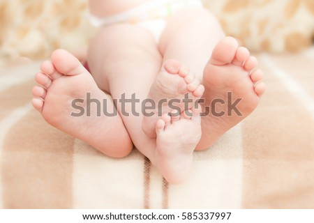 Little kids feet, covered with prints from kisses, children playing on tablet