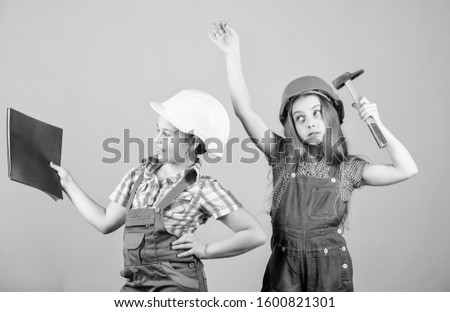 Little kids in helmet with tablet and hammer. small girls repairing together in workshop. happy children. Future career. Labor day. 1 may. Foreman inspector. Repair. working day. ordinary working day.