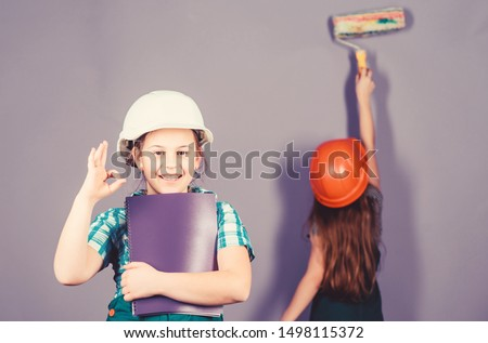 Little kids in helmet with tablet and roller. engineering idea. Future career. Painting wall. Foreman inspector. Labor day. 1 may. small girls repairing together in workshop. Trust me I am an expert.