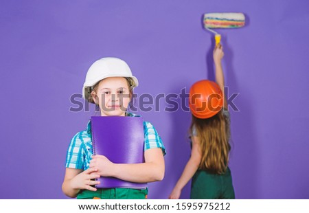 Little kids in helmet with tablet and roller. Labor day. 1 may. engineering idea. Future career. Painting wall. Foreman inspector. Repair. small girls repairing together in workshop. working day.