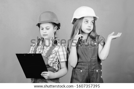 Little kids in helmet with tablet. small girls repairing together in workshop. school project. Labor day. 1 may. Foreman inspector. Repair. Tired mechanic. Now I see the problem.