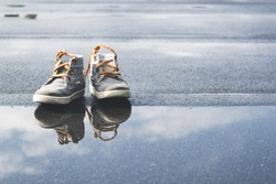 Little kids laced shoes close to a puddle with water. Shoes reflecting in water. Blue sky and clouds reflecting in water.
