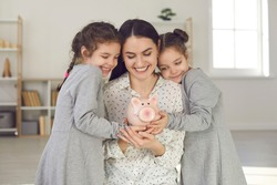 Little kids learning to value money. Happy young single mother and two cute daughters holding piggy bank and smiling. Saving up for children's education, family finance, and budget management concept