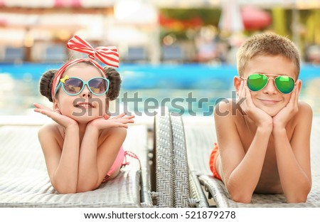 Little kids lying on deck chairs on sunny day