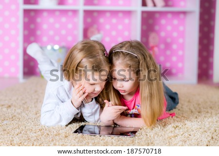 Little kids playing on a tablet computing device - laying on the floor in the pink room