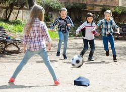 Little kids playing street football outdoors in spring day