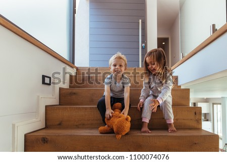 Little kids sitting on stairway, with boy grabbing a teddy bear. Sibling playing with teddy bear on staircase at home.