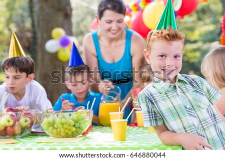 Little kids with birthday hats having fun on a garden party #646880044