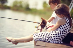 Little kids with dog sitting on a wood pier and fishing in a pond.