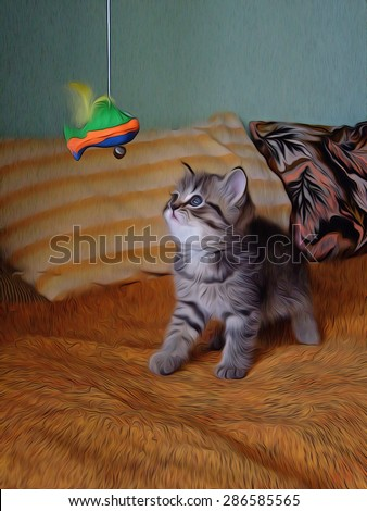 Little kitty playing with a toy fish on the bed