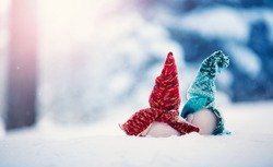 Little knitted snowmen on soft snow on blue background. Back view. Christmas concept.