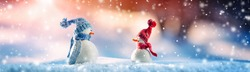 Little knitted snowmen on soft snow on blue background in winter on snowfall