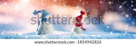 Photo of  Little knitted snowmen on soft snow on blue background in winter on snowfall