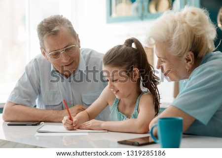 Little lady drawing a picture with grandma and grandad. Family's hapiness, fun time and being together.