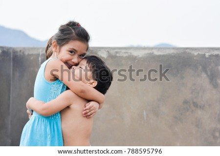Little latin siblings hugging.