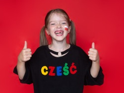 little laughing  girl showing thumbs up , on her sweatshirt the word Hello in Polish, the advertising concept of the Polish school, the study of the Polish language