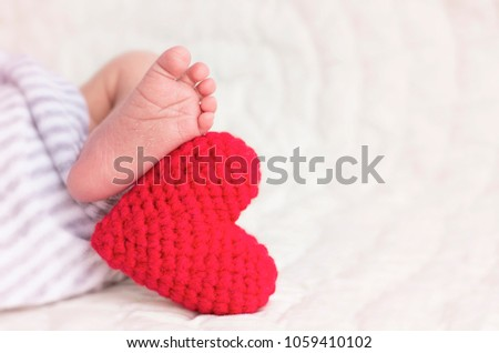 Little Legs of newborn baby sleeping lie on a knitted red toy heart.