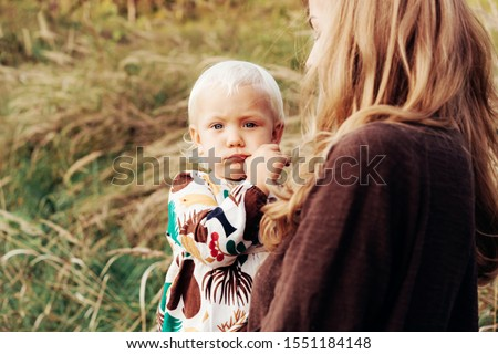 Little little caucasian girl toddler in arms her mother outside. The child builds a disgruntled grimace. Innocent facial expressions of childish immediacy. Tender caring motherly hugs. #1551184148
