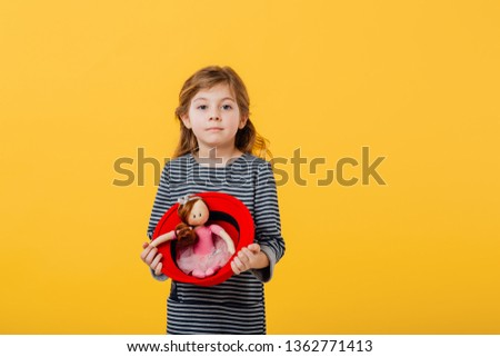 little little girl and beautiful with a doll in red hat, dressed in striped coat, isolated on yellow background, copy space